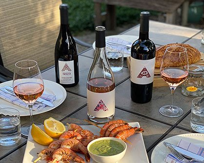 Parrillada Pack: Artesa Tempranillo, Rosado and Pinot Noir on a table setting with grilled shirmp, bread, wine glasses and table settings