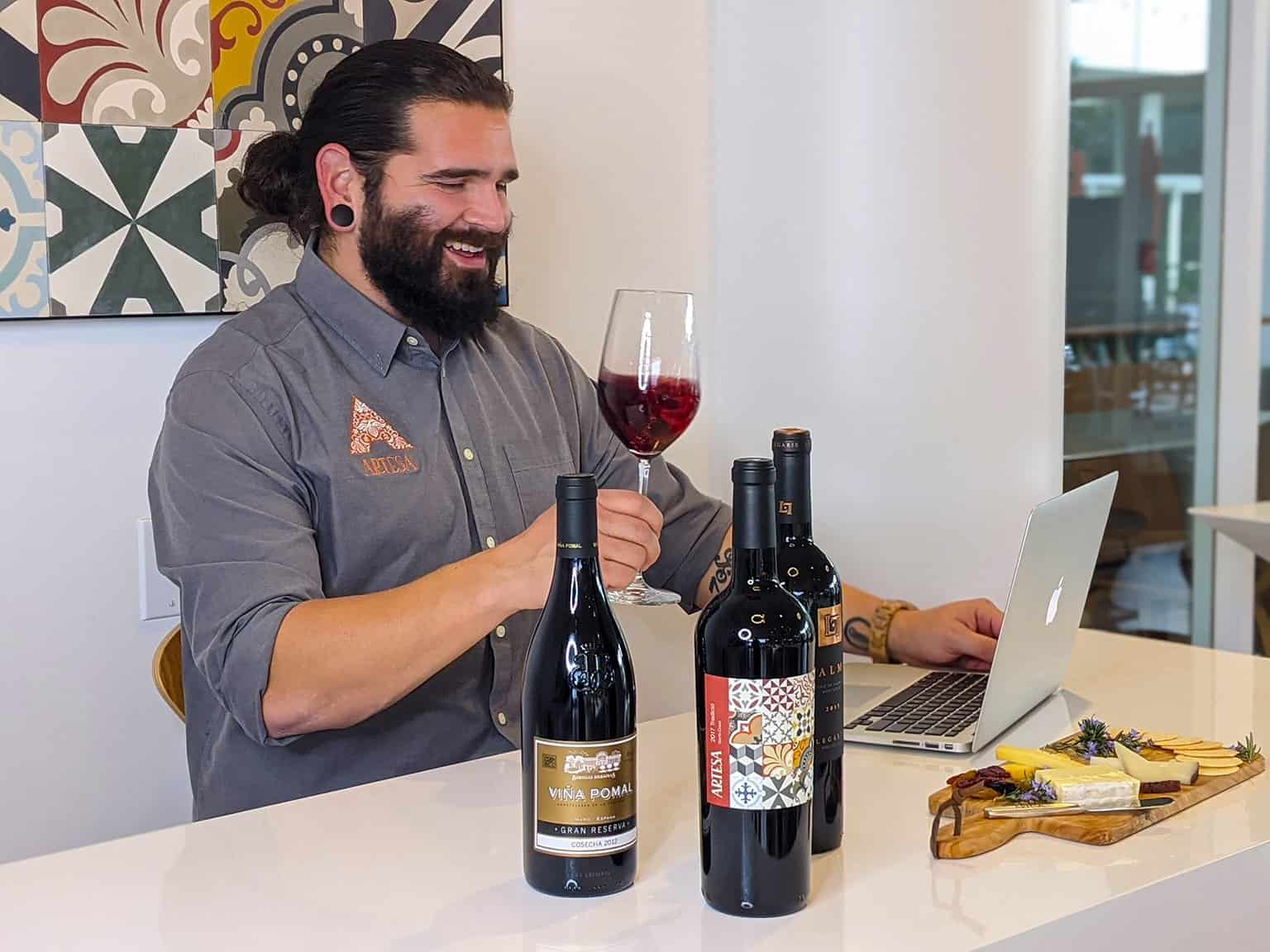 Wine Educator hosting virtual event with glass of wine in hands